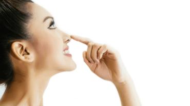 mulher branca com o indicador na ponta do nariz após plástica