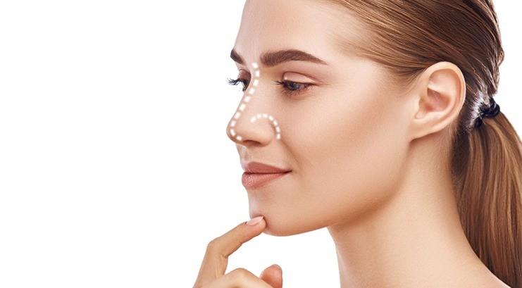 Rosto de mulher ruiva com o dedo indicador no queixo e maior destaque no nariz.